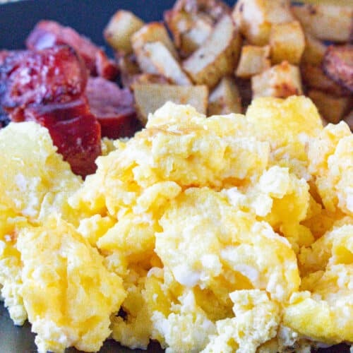 Scrambled eggs in air fryer on black plate with sausage and potatoes