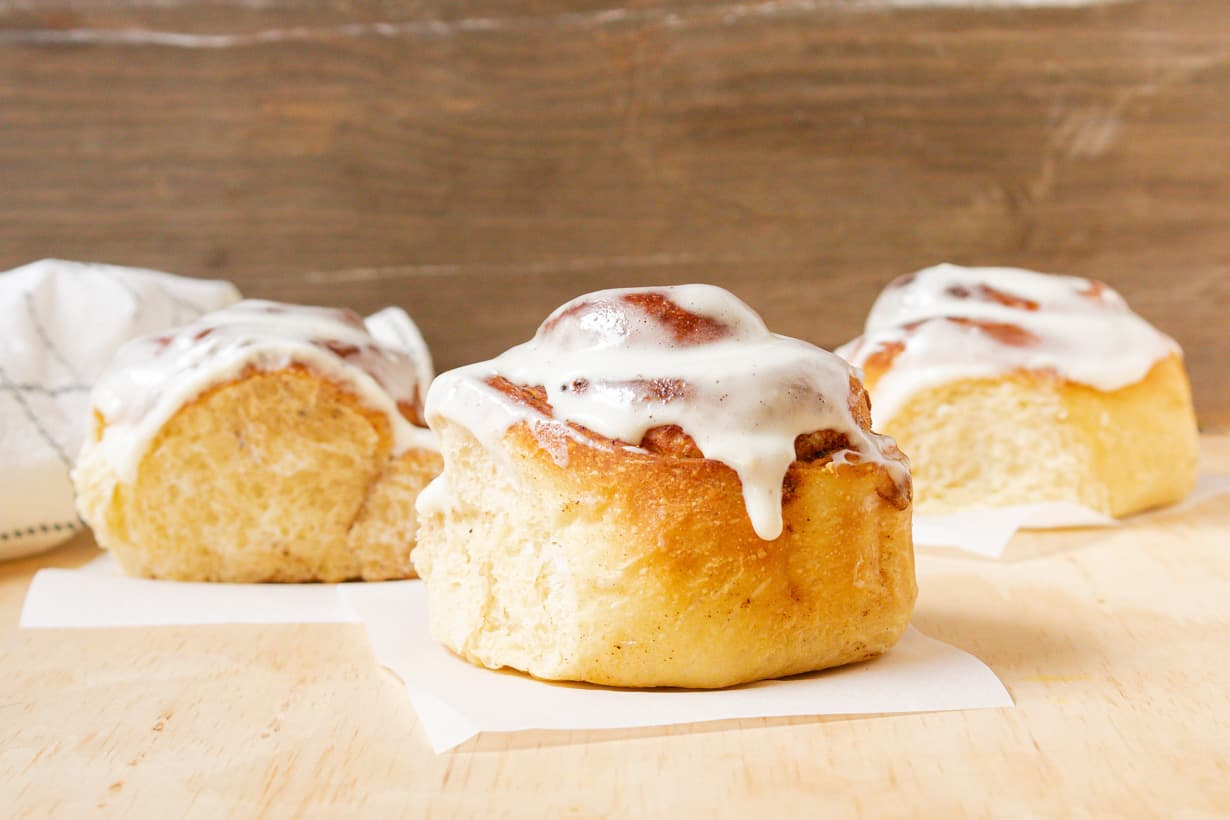 air fryer cinnamon rolls on parchment paper and wooden table