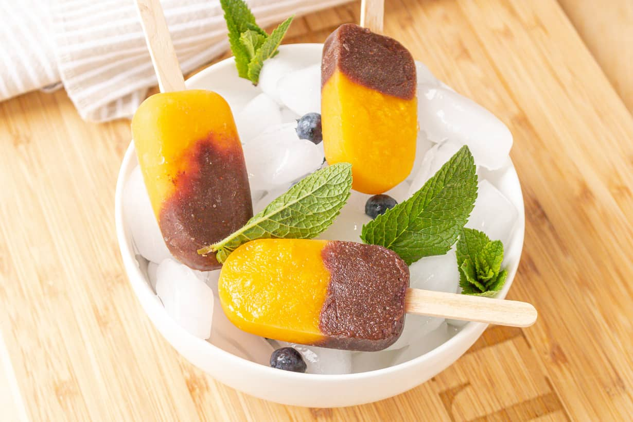 mango pops in bowl of ice with mint and blueberries