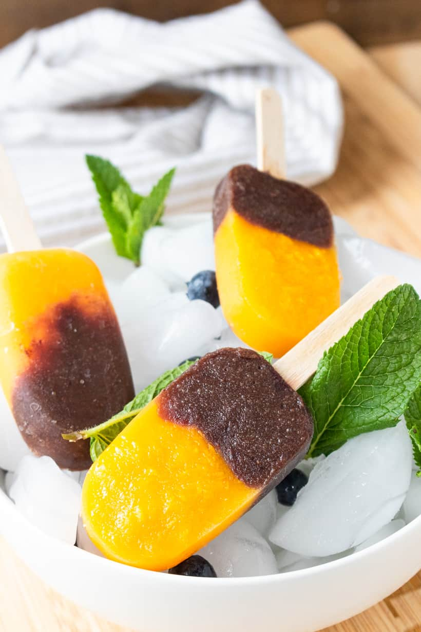 close up view of mango pops in bowl of ice with mint and blueberries