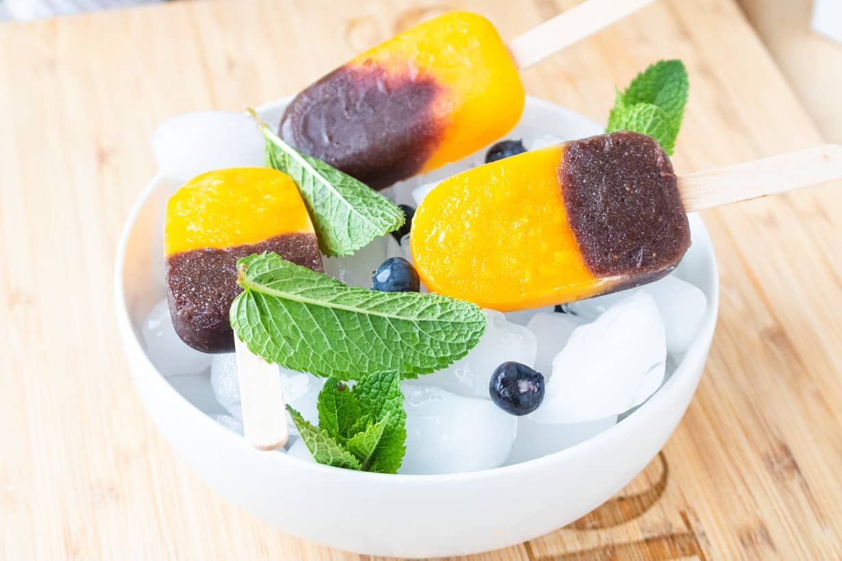 mango popsicles in bowl of ice with blueberries and mint