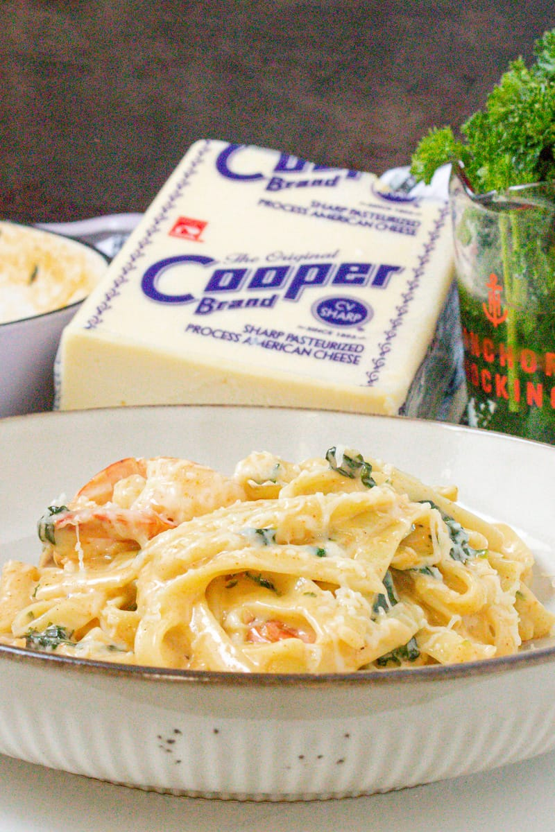 Alfredo spinach with shrimp and Cooper cheese in the background
