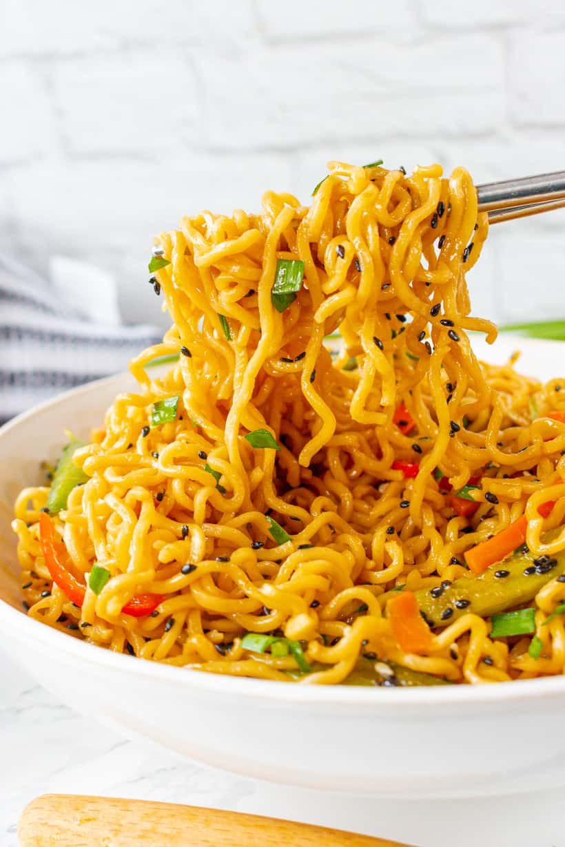 lo mein noodles in white bowl with silver chopsticks.