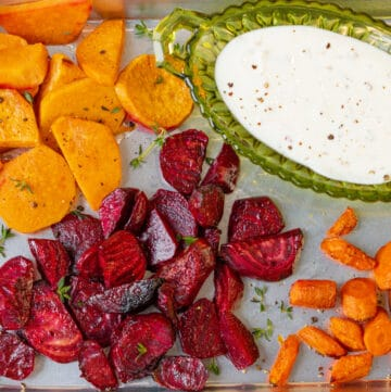 air fryer roasted vegetables in baking tray with yogurt sauce
