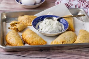 empanadas in tray with sauce
